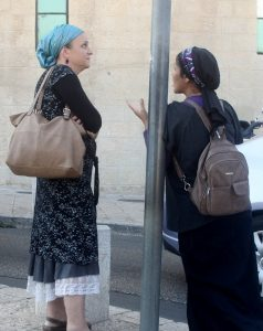Two women standing by a pole having a conversation