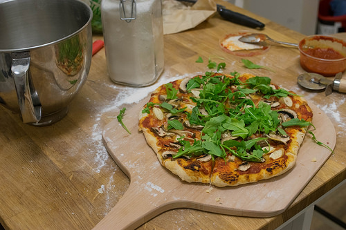 Image of a pizza peel with mushroom and arugula.