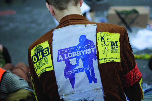 "An image of the back a person wearing a jacket. A patch on the jacket reads ""I can't afford a lobbyist""."