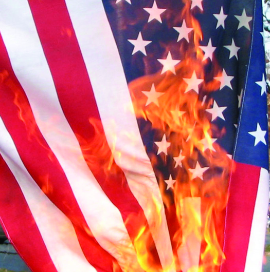A photo of an American flag. The flag is on fire.