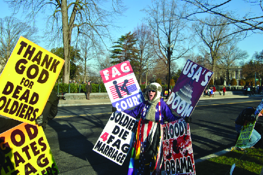 "A photo of people holding signs. The signs read ""Thank God for dead soldiers"", ""God hates—"", ""Fag Court"", ""Soldiers die 4 fag marriage"", ""USA's doom,"" and ""Bloody Obama""."