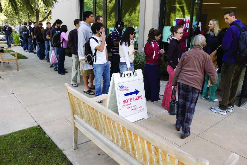 "An image of several people standing in line outside of a building. A sign near the front of the line and the building entrance reads ""Vote Here""."